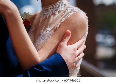 A young man gently embraces his bride in a wedding dress by the shoulders to the goosebumps. Bride & bridegroom. Groom kisses bride's neck.