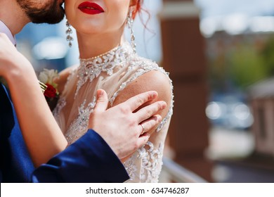 A young man gently embraces his bride in a wedding dress by the shoulders to the goosebumps. Bride & bridegroom. Groom kisses bride's neck. Girl with red lips.