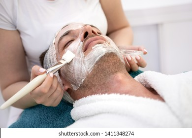 Young  man getting a facemask at the spa - beauty treatment concepts