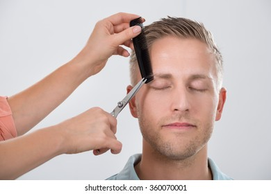 Young man getting his eyebrow trimmed by female hairdresser against white background