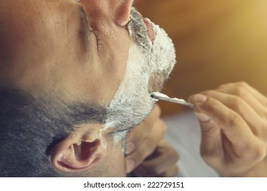 Young man getting an old-fashioned shave with straight razor. Closeup, retro styled imagery