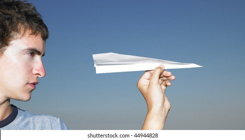 Young man getting ready to throw a paper airplane. Horizontal shot.