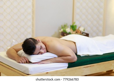 Young man getting Thai massage on mattress in the room at Spa and Massage. swedish oil spa.
