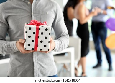 Young man with gift box at birthday party in office