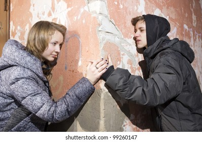 The young man and the girl at an old wall
