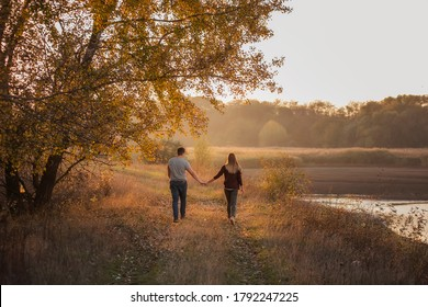 A young man and a girl are walking  in the autumn forest next to the lake. Couple in love  spend time forever together. Traveling during the cold season, on weekend days. Happy lovers hold hands, kiss