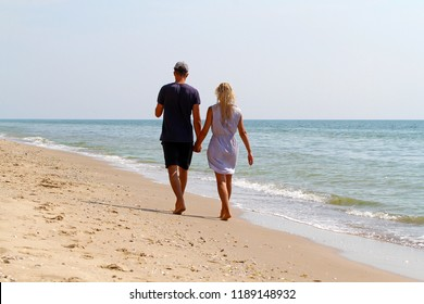 A young man and a girl with wet blond hair walk barefoot along the sandy beach from behind. A loving couple are walking along the seashore leaving the photographer ahead
