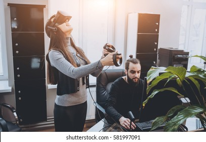The young man with girlfriend plays a game at the office. Virtual reality