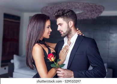 Young man give rose to lover indoor, couple in love