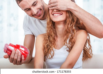 young man gives her a heart shaped gift, valentines day theme