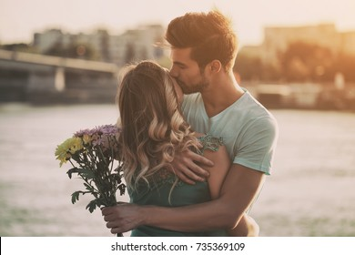 Young man is giving beautiful bouquet of flowers to his girlfriend.Happy couple   Image is intentionally toned.