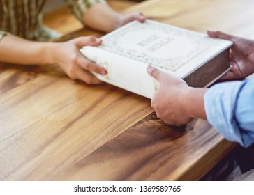A young man giving big old book of holy bible to his friend on wood table in working place. Christian background,  share the world of God or gospel concept with copy space.