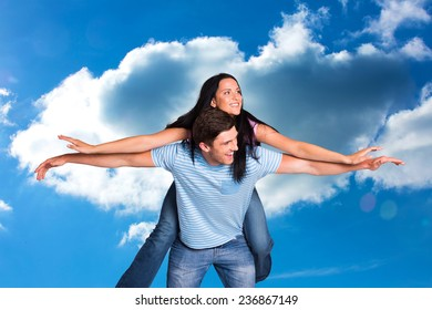 Young man giving girlfriend a piggyback ride against cloudy sky