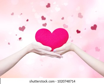 Young man giving a heart-shaped pillow his sweetheart on Valentine's Day. Love beautiful concept isolated on pink pastel heart bokeh happy concept background.