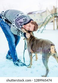 A young man giving his dog cuddles and affection during a walk in the snow at the park on a bright sunny day.