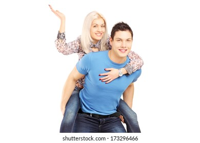 Young man giving his girlfriend a piggy back ride, isolated against white background