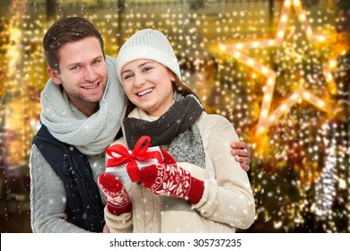 Young man giving his girlfriend Christmas present in front of holiday lighting