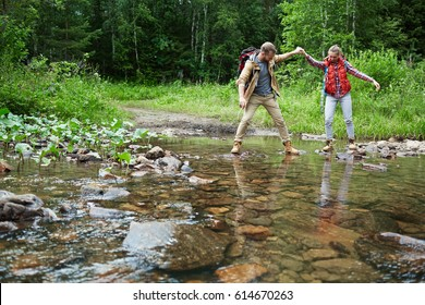 Young man giving his girlfriend helping hand while crossing river
