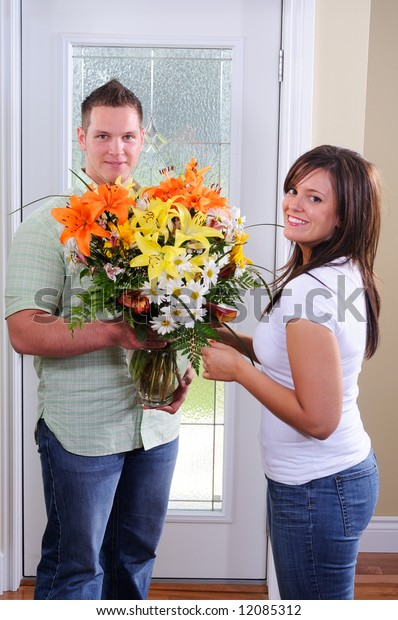 Young Man Giving His Wife A Flower Arrangement, (focus on the man)