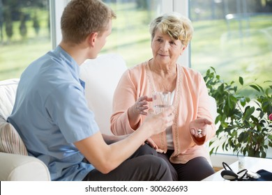 Young man giving medications to an older woman