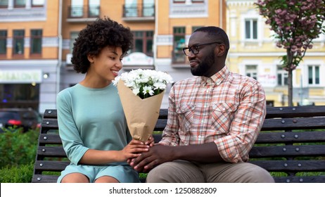 Young man giving white flower bouquet to woman sitting bench, first awkward date