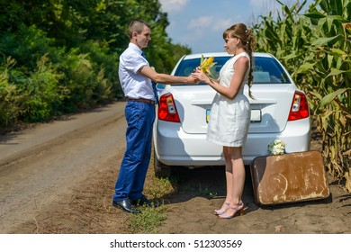 Young man giving a woman an ear of corn near rear of white automobile near cornfield