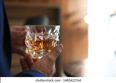 Young man with glass of whiskey indoors, closeup view. Space for text