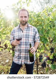 Young man with glass of wine in a vineyard