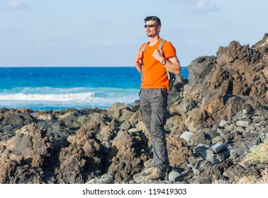Young man in glasses with backpack. Backround blue sea