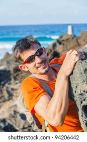 Young man in glasses with backpack climbing indoor wall. Backround sea