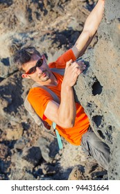 Young man in glasses with backpack climbing indoor wall. Vertical view