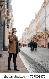 Young man in glasses and brown coat with the black purse posing in the city and holding his mobile smartphone