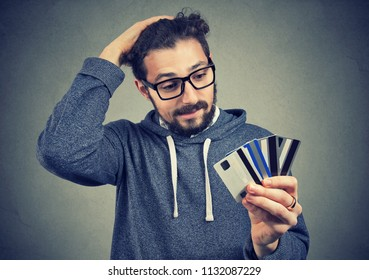 Young man in glasses holding credit cards and looking stressed with increasing debt