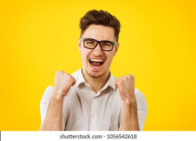 Young man in glasses holding hands fists up celebrating success on orange yelllow background.