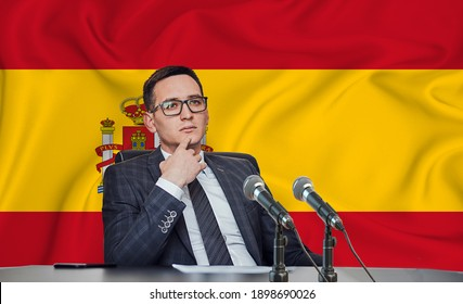 Young man in glasses and a jacket at an international meeting or press conference negotiations, on the background of the flag Spain