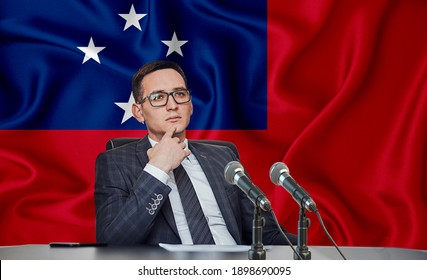 Young man in glasses and a jacket at an international meeting or press conference negotiations, on the background of the flag Samoa