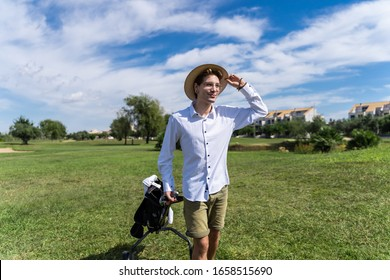 Young man with glasses and piercings with his hand in his hat on a golf course on a sunny day dragging a golf cart in