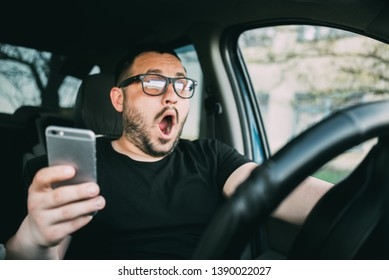 A young man in glasses sitting in the car, screaming, distracted by the smartphone is very scared
