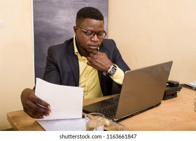 young man in glasses sitting at desk looking at laptop.