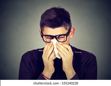 Young man in glasses sneezing in a tissue blowing his runny nose