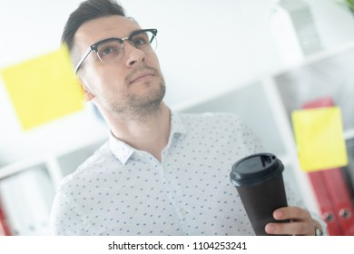 A young man in glasses stands near a board with stickers and holds a glass of coffee in his hands.
