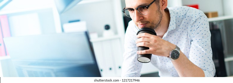 A young man in glasses stands near a table in the office, holds a glass of coffee in his hand and works with a computer.