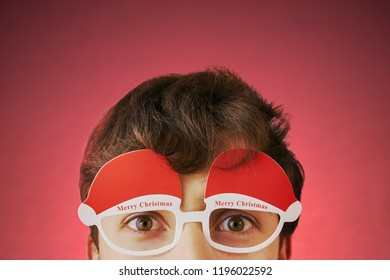Young man with glasses with text merry Christmas on a bright red background. Holiday costume