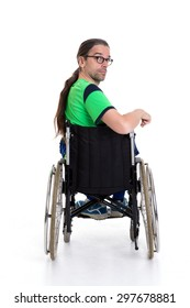 young man with glasses in a wheelchair in front of white background from the back