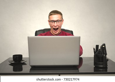 A young man in glasses and with wide open mouth working at a laptop at the table and in shock from what he saw. Man Looks amazing movie. Gamer playes in game. Special offer. Big sale.