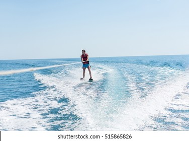 Young man glides on water skiing on the waves on the sea, ocean. Healthy lifestyle. Positive human emotions, joy. Family are kayaking at tropical ocean in the day time. Spring and summer holidays.