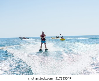 Young man glides on water skiing on the waves on the sea, ocean. Healthy lifestyle. Positive human emotions, feelings, joy. Spring and summer holidays.