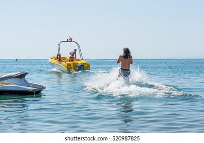 Young man glides on water skiing on the waves on the sea, ocean. Healthy lifestyle. Positive human emotions, feelings, joy. Funny cute boy making vacations and enjoying summer.