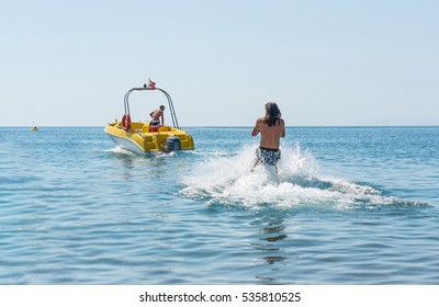 Young man glides on water skiing on the waves on the sea, ocean. Healthy lifestyle. Positive human emotions, joy. Funny cute boy making vacations and enjoying summer. Spring and summer holidays.