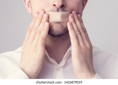 Young man glues his mouth with a plaster, force yourself to shut up, close up, concept of secrecy, toned